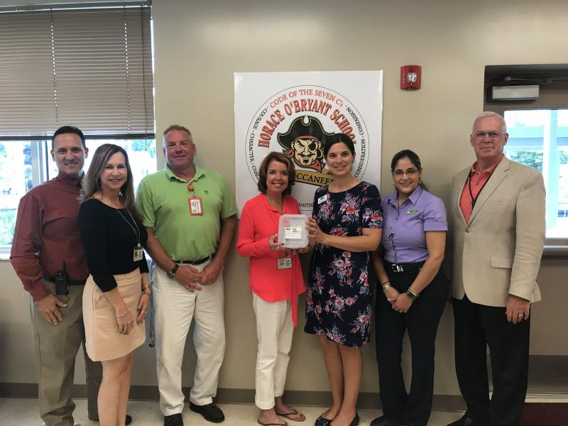Horace O'Bryant staff and Superintendent Mark Porter accept Tools for Back to School gift cards from UWFK & Publix staff.