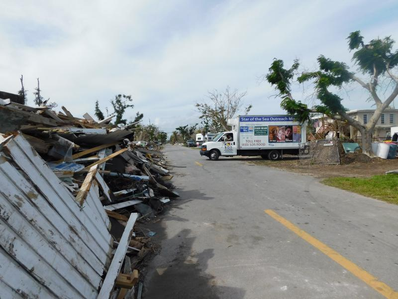 Here SOS delivers fresh mattresses in a devastated neighborhood.